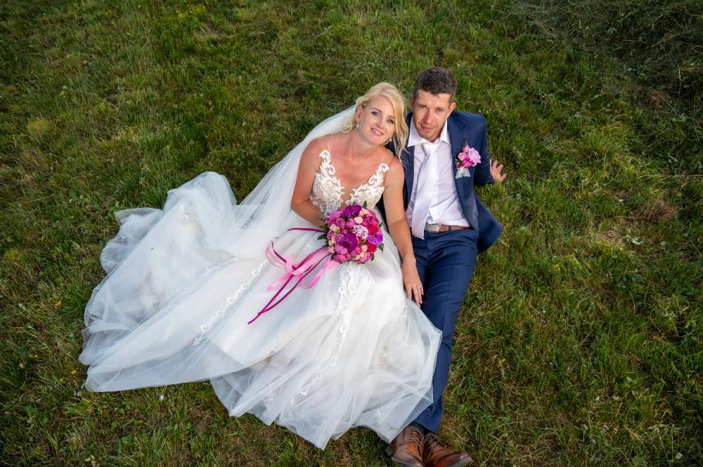Ženich a nevěsta sedí na louce