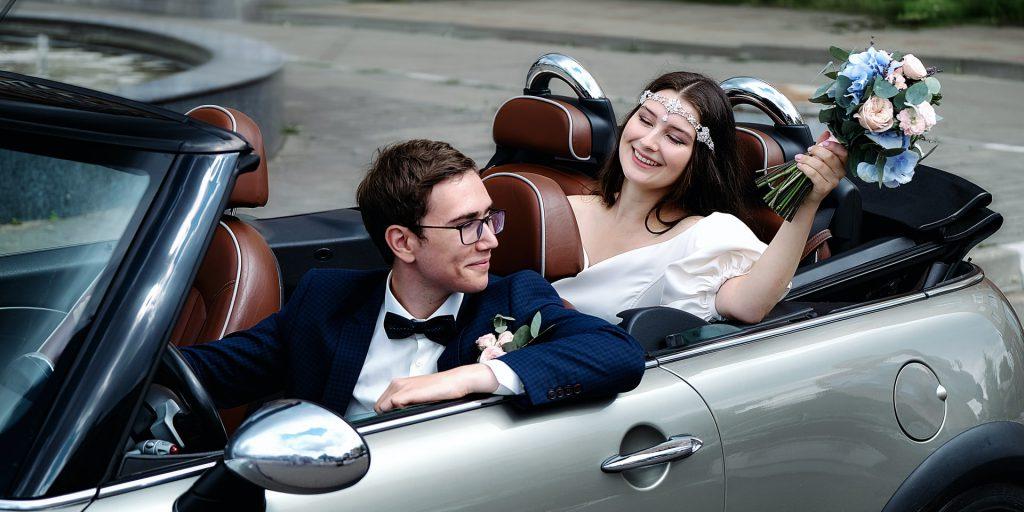 Svatební auto, ženich a nevěsta v autě.